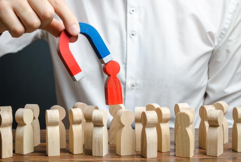 商人拔出一个红色图从人群的一个人在磁铁帮助下 领导处理事务并且形成队 图库摄影