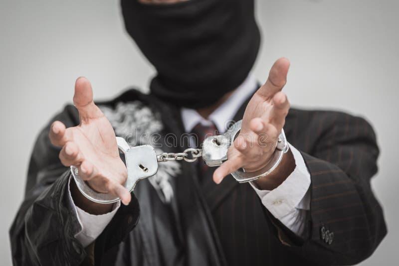 商人拘捕与金钱欧元金钱银行欺骗和贿赂的手铐 大开的手 图库摄影