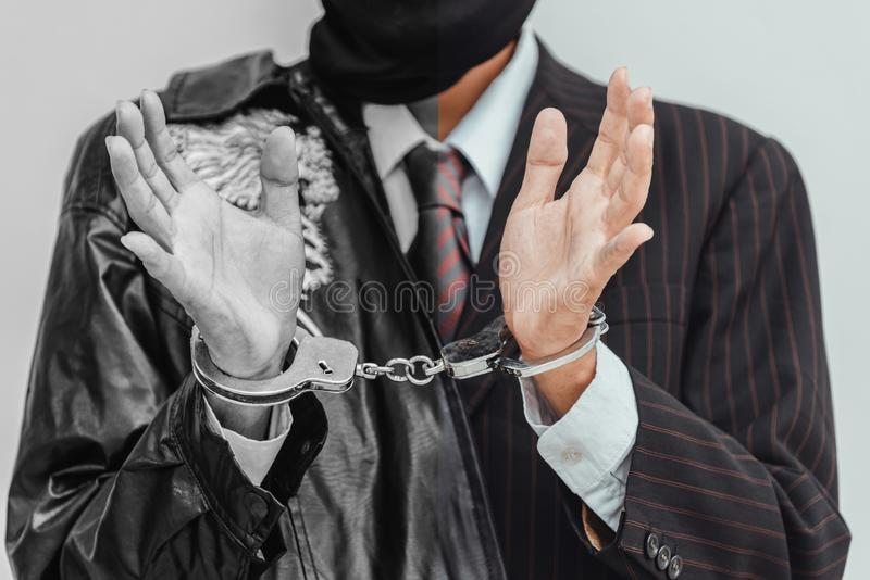 商人拘捕了并且扣上了手铐,因为做非法生意,有对黑暗的企业概念的黑背景 免版税库存图片