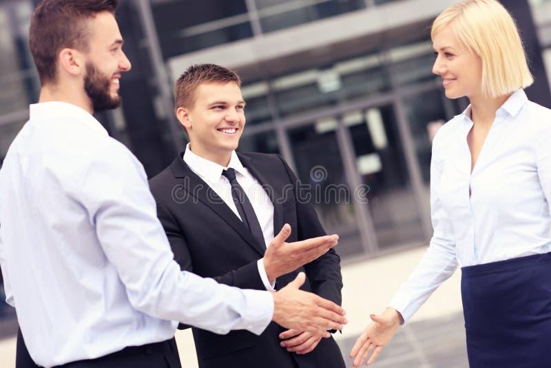 商人招呼在现代大厦之外 免版税库存图片