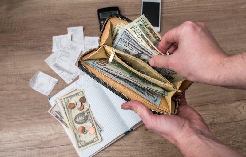 商人拿着有美元的一个钱包在背景笔记本 免版税图库摄影