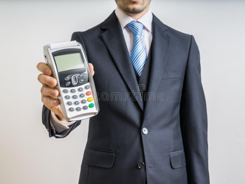 商人拿着付款终端手中 免版税图库摄影