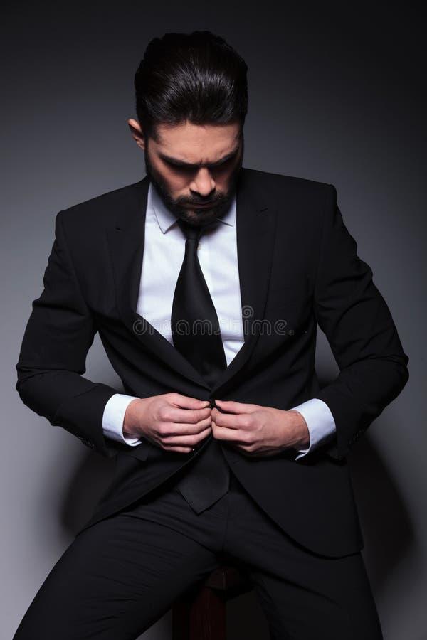 年轻商人按他的夹克 免版税库存图片