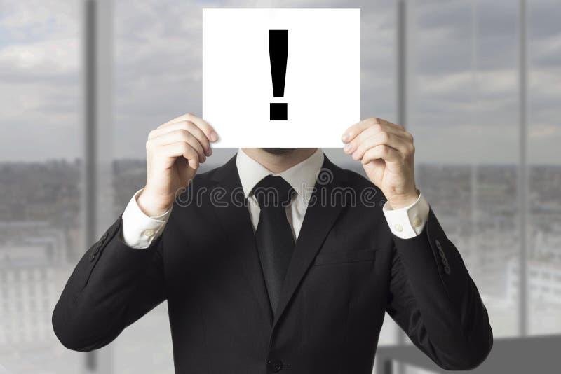 商人掩藏的面孔惊叹号 库存照片