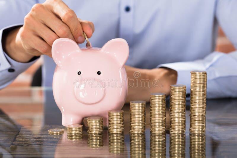 商人插入物硬币在存钱罐中 库存图片