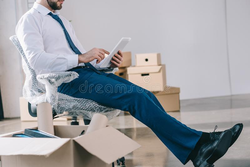 商人播种的射击使用数字式片剂的,当坐在新的办公室时 库存图片