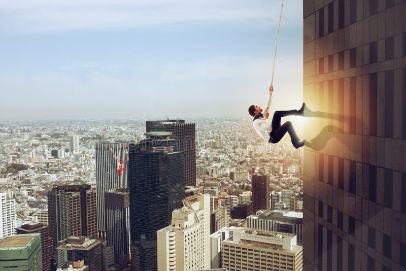 商人攀登与绳索的一个大厦 决心的概念 免版税库存照片