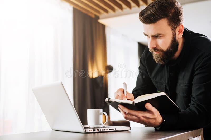 商人支持计算机,看膝上型计算机屏幕,做在笔记本的笔记 人观看webinar,学会 库存照片