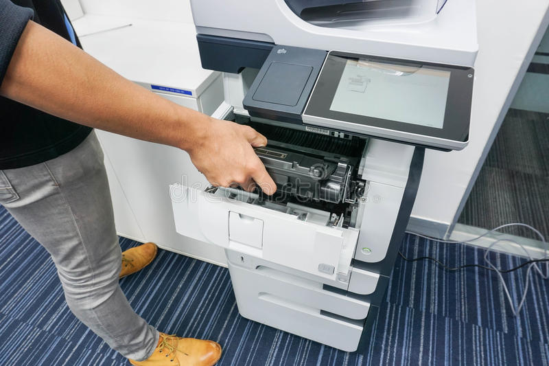 商人放墨盒入打印机 免版税库存图片