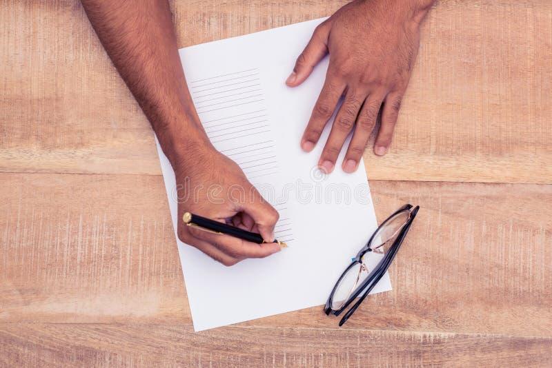 商人文字的播种的手在纸的由在书桌的眼睛玻璃 免版税图库摄影