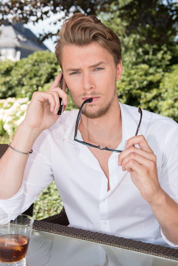 年轻商人是在电话在庭院里 免版税库存照片