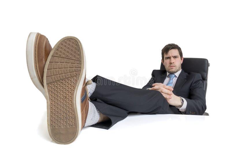 年轻商人是松弛在工作场所并且有他的在书桌上的脚 背景查出的白色 库存照片