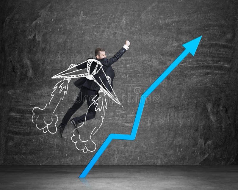 商人是采取对与拉长的翼的成功 迅速上升的蓝色箭头 免版税库存图片