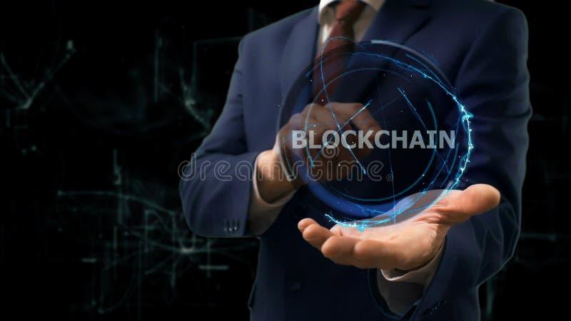 商人显示在他的手上的概念全息图Blockchain 免版税图库摄影