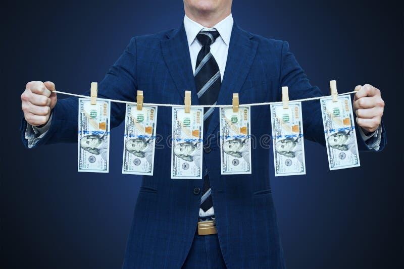 商人显示贪污来的钱 拿着金钱的商人垂悬在绳索 免版税库存照片