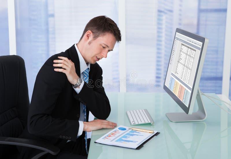 商人有肩膀痛苦在计算机书桌 免版税库存图片