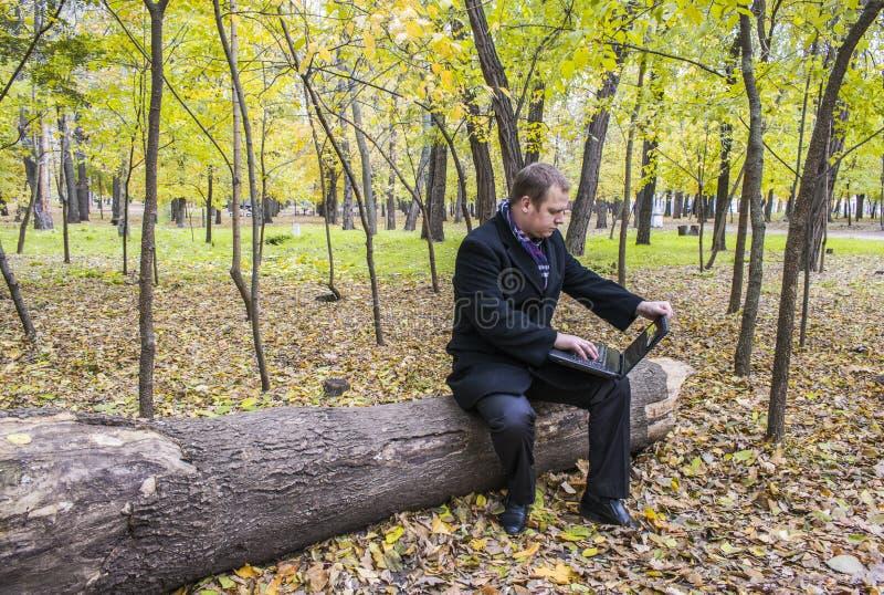 商人有膝上型计算机在秋天的公园 一个人工作在一台计算机在公园 图库摄影