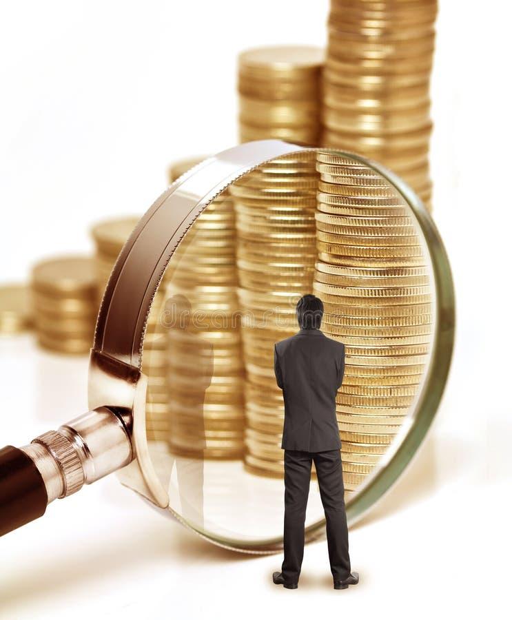 商人检查金钱与放大镜 免版税库存图片