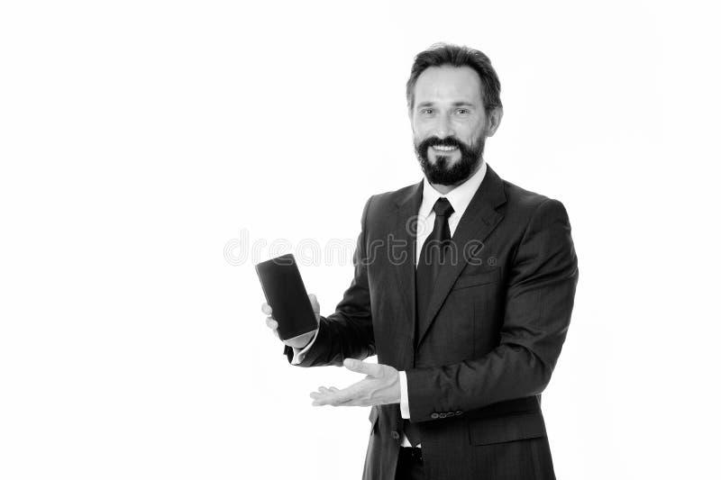 商人正式衣服拿着智能手机 高兴人有胡子的商人宣布新版本更新应用 检查 图库摄影