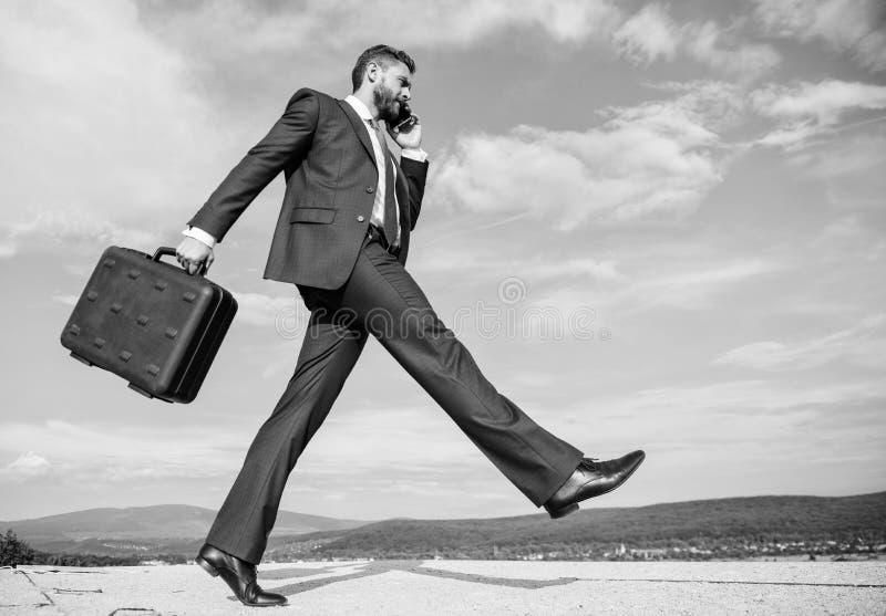 商人正式衣服运载公文包天空背景 解决在电话的商人业务问题 不要停止 库存照片