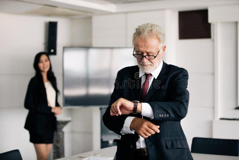 商人注视着手表和女商人微笑愉快为工作 库存图片