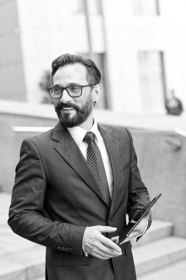 商人特写镜头使用一种数字片剂的在工作 英俊的有胡子的商人画象在见面的室外 库存照片