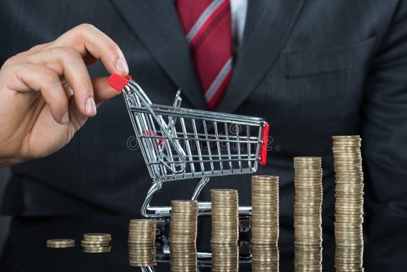 商人特写镜头与堆的硬币和购物车 免版税图库摄影