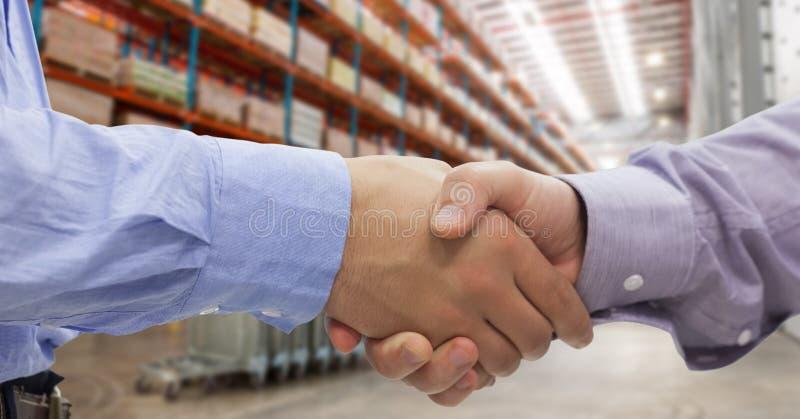 商人特写镜头握手的在仓库里 库存照片