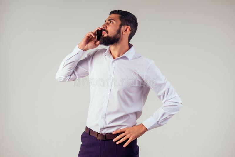 商人理发店老板使用手机 白人留着胡子的年轻男子拿着智能手机做生意 图库摄影