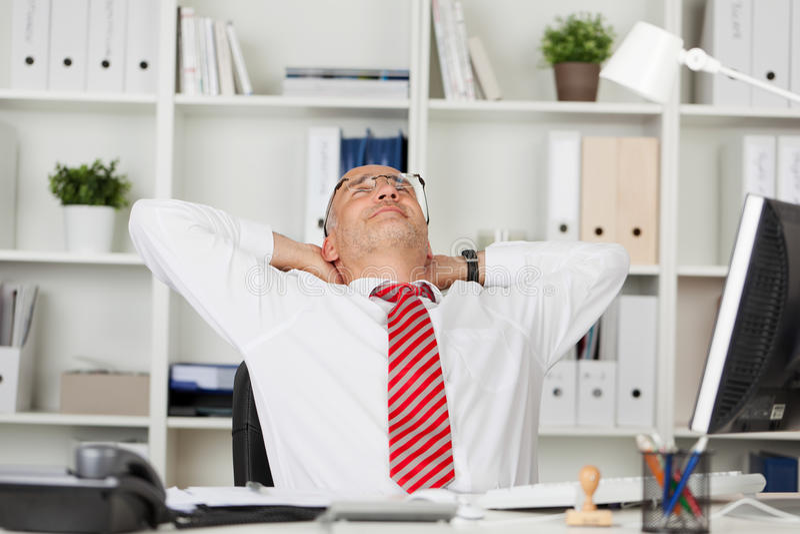 商人用在头后的手在书桌 库存照片