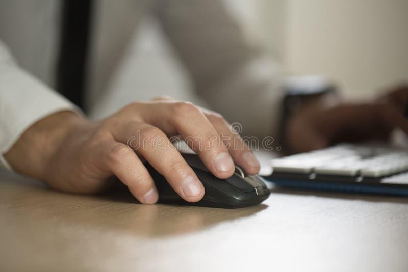 商人用途计算机老鼠和键入的手,合作a 库存图片