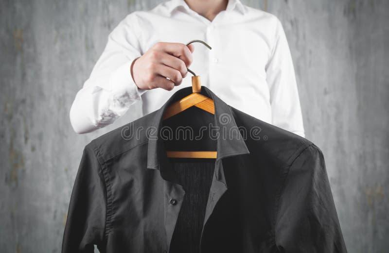 商人用黑色衬衫吊架 免版税库存照片