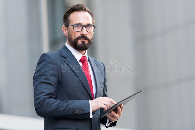 商人画象与片剂的在手中在办公楼背景  使用片剂的商人室外与4G 免版税库存图片