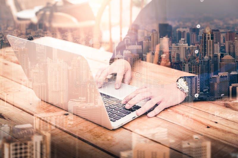 商人的两次曝光图象使用一手提电脑的在日出期间躺在与都市风景图象 ??  免版税库存照片