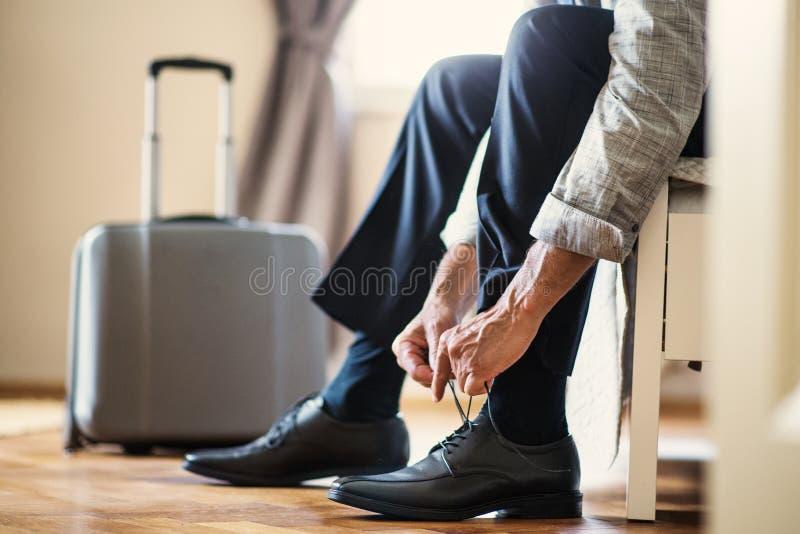 商人的中央部位在坐在酒店房间的出差的,栓鞋带 免版税库存照片