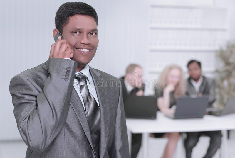 商人的前景谈话在一个手机在办公室 免版税图库摄影