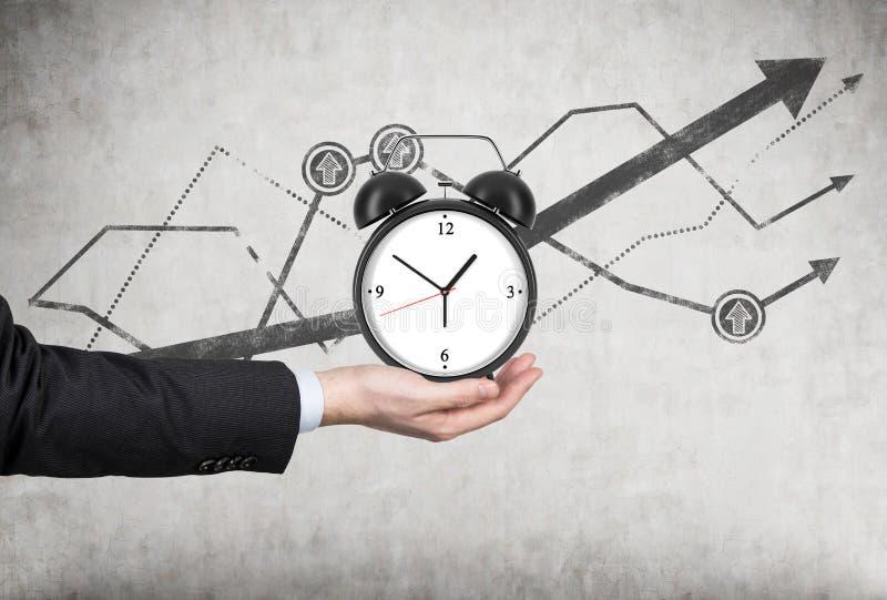 商人的手拿着一个闹钟 有在闹钟后的生长折线图 时间安排的概念或 库存照片