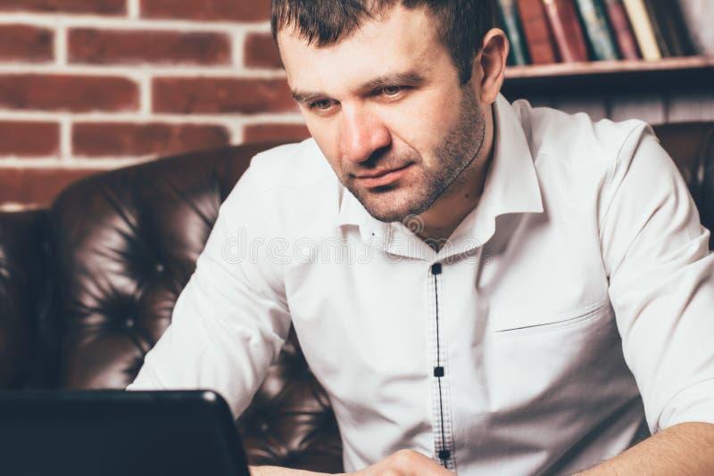 商人的神色被束缚到膝上型计算机 一个人在工作被吸收在他的事务 库存图片