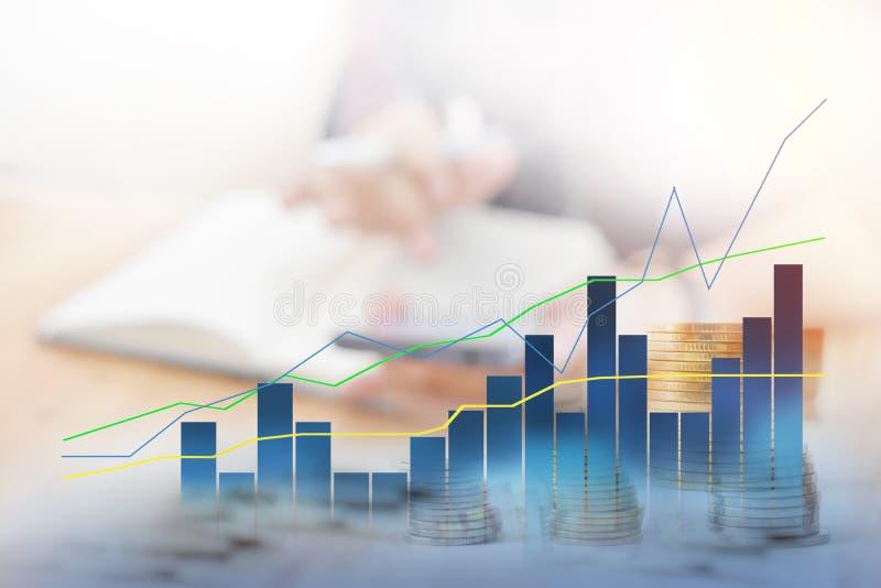 商人的背景迷离坐工作 前景是图表,统计表明正向 免版税图库摄影