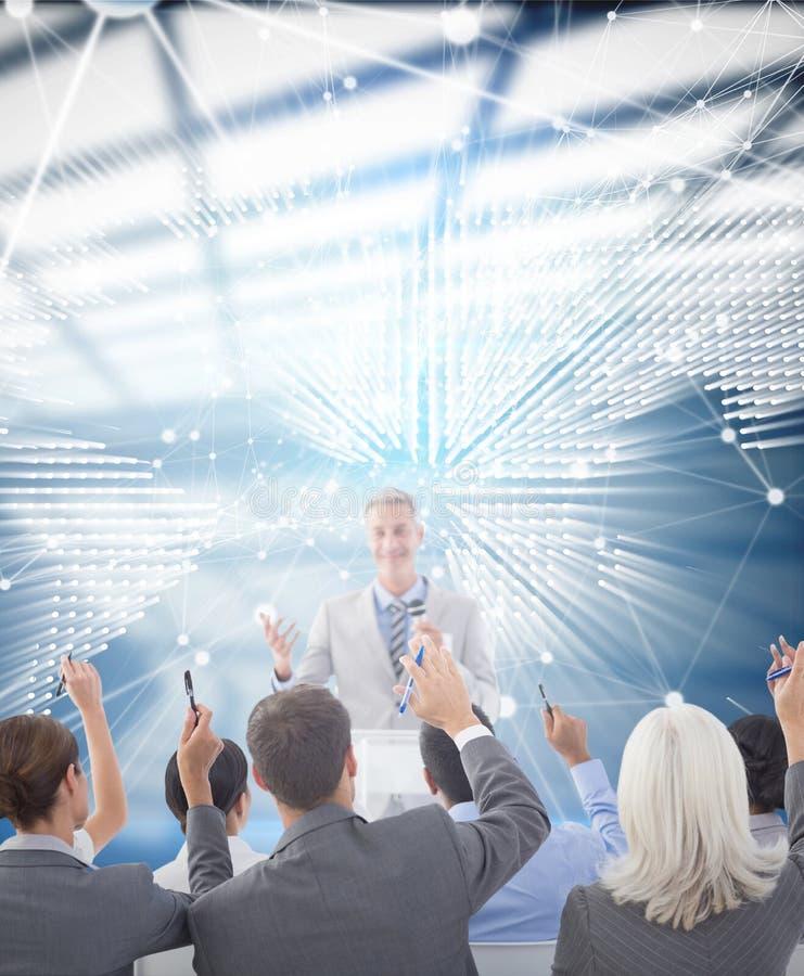 商人的综合图象举他们的胳膊的在会议期间 免版税库存图片