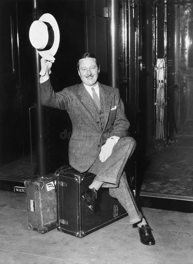 商人的画象坐他的在一个平台的手提箱在火车前面(所有人被描述不是更长的生活 免版税库存图片
