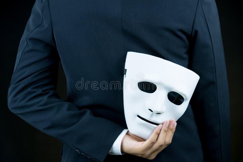 商人皮白色面具在他的后面后的手上在b 免版税库存照片