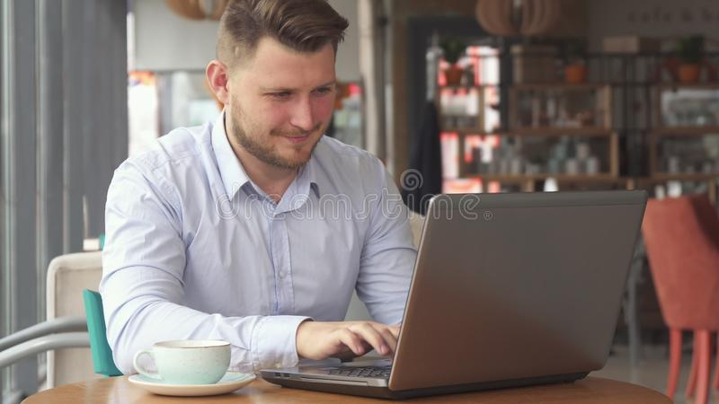 商人研究膝上型计算机在咖啡馆 库存照片