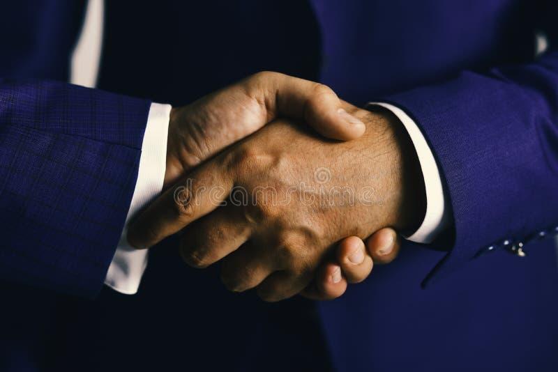 商人穿着聪明的衣服 生意和协议概念 紧紧震动男性的手 在浅灰色的握手 图库摄影