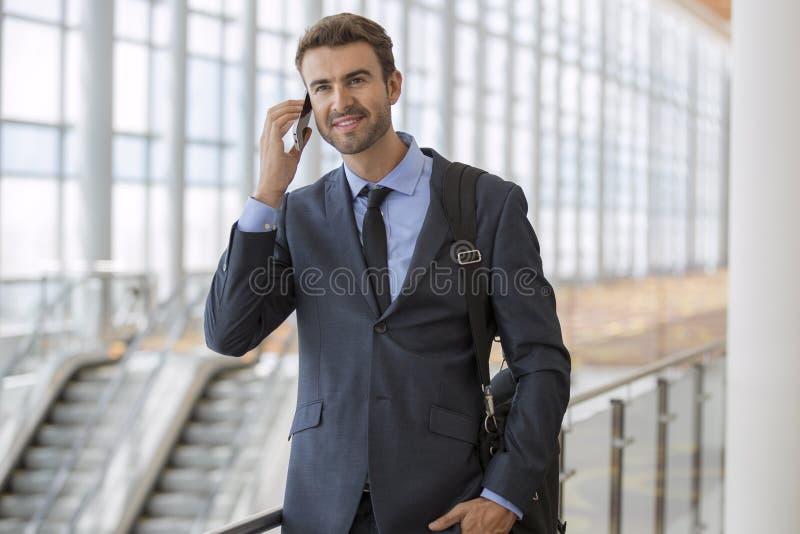 商人站立的走的谈话在他的手机 库存图片