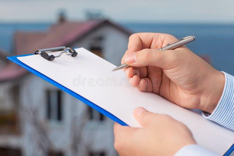 商人签署在公寓b的背景的一个文件 免版税库存照片