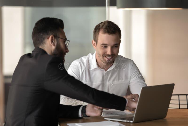 商人经理咨询的客户,指向膝上型计算机屏幕 免版税图库摄影