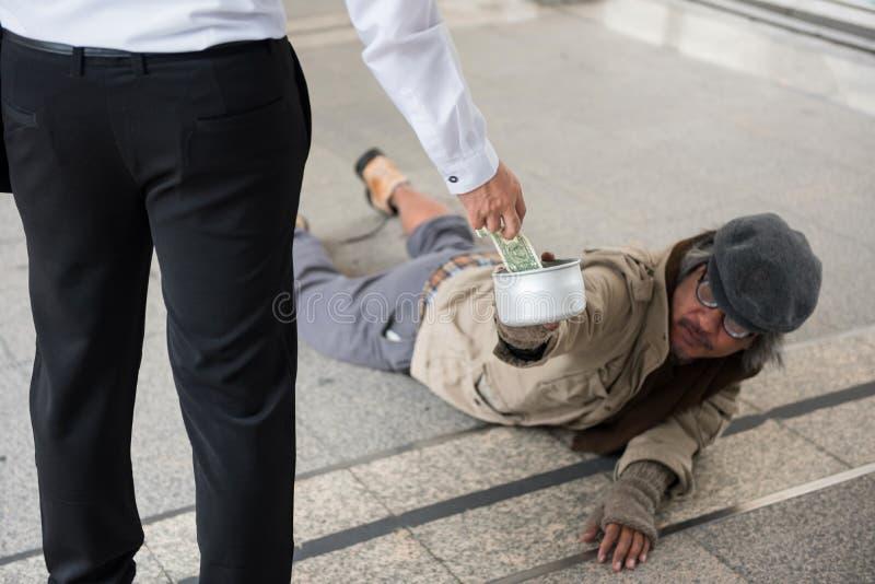 商人给有残障的无家可归的人捐钱 免版税库存图片