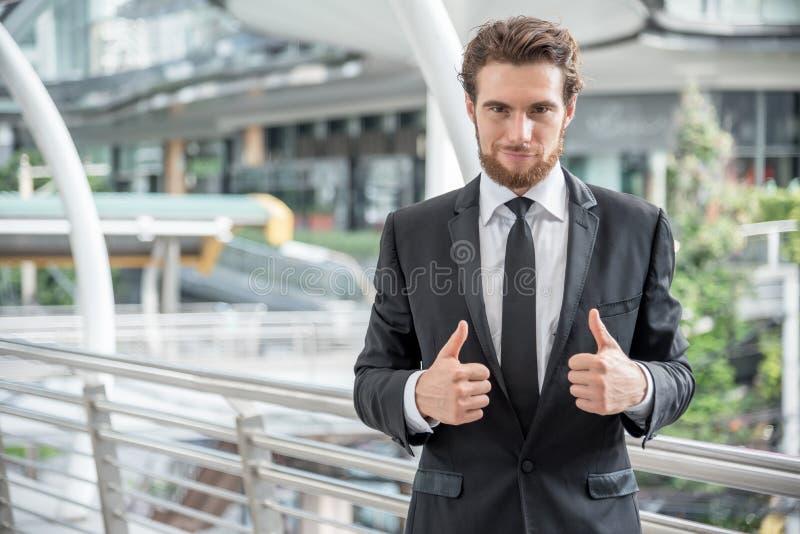 商人给翘拇指,企业概念,快乐的概念 免版税库存照片
