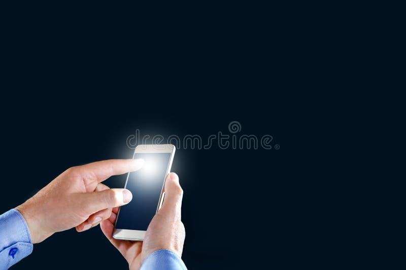 商人网络的触摸屏智能手机的手在黑背景 免版税图库摄影